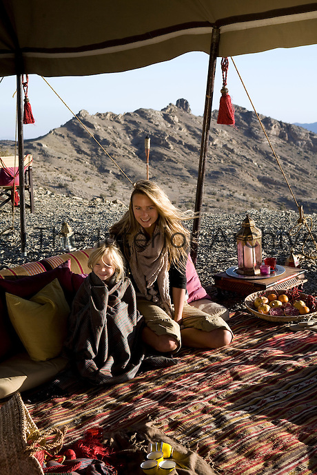 Portrait of a mother and daughter sitting in the camp's communal area under a large awning