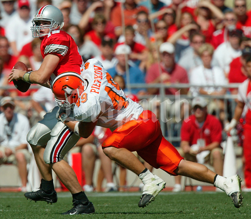 Ohio State's quarterback Scott McMullen, 15, looks down field as he gets sacked by Bowling Green's Ted Piepkow, 49, in the third quarter of their game at The Ohio Stadium, September 20, 2003.  (Dispatch photo by Neal C. Lauron)