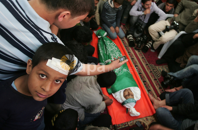 Palestinians sit next to the body of the boy Mahmoud Al-Jaroh who was killed in an Israeli air Strike on Friday, during his funeral at a mosque in Gaza City April 9, 2011. Militant group Hamas said on Saturday it would escalate it attacks against Israel to include a wider range of targets if Israel failed to halt its aerial assaults on the Gaza Strip. Photo by Mohammed Othman