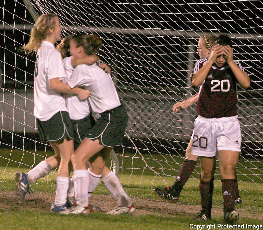 02/05/06..... Gary Wilcox/The Times-Union.......St. Augustine's Aja Ammar (cq) (#20) walks away from the net as   Nease celebrate after  Casey Eckstein  (#0) , score the winning point at the  Nease High School vs. St. Augustine High School  girls soccer  Region 2-4A Final, at Nease High School last Friday night.(02/03/06)   Nease won 2 to 1.