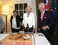 17 May 2016 - London, England - Camilla Duchess of Cornwall cutting a cake with Selwyn Image, founder of Emmaus UK, at a reception to celebrate the 25th anniversary of the charity - which supports former homeless people by giving them a home within one of its Emmaus Communities - at the French Ambassador's Residence in Kensington, London. Photo Credit: ALPR/AdMedia