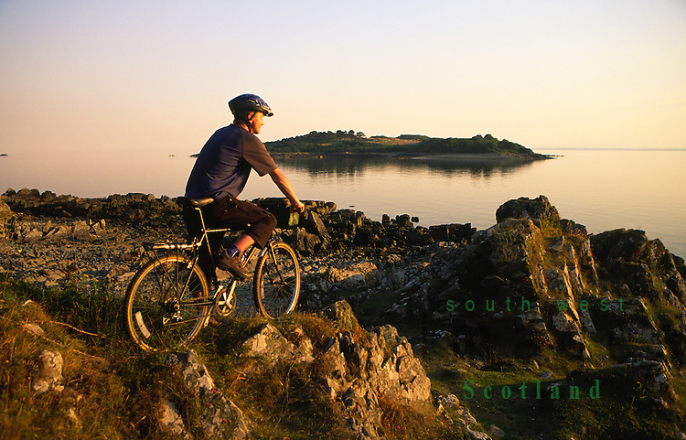 Cyclist admiring the view out to Ardwall Isle on Wigtown Bay Solway Firth from near Carrick near sunset Dumfries and Galloway Scotland UK