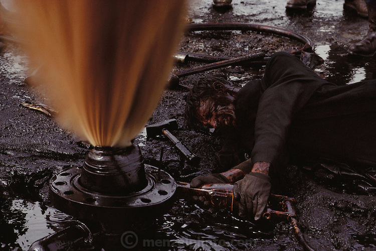 An oil well fire specialist of Red Adair, Co. of Texas works to prepare a well for capping by sawing off the damaged well head in the Kuwait oil fields. The fire has already been extinguished but the well is spewing oil and gas into the air under high pressure. The trick is to cut through the metal casing cleanly without causing any sparks that could reignite the well and incinerate the workers. The company was one of those brought in to fight the Kuwait oil well fires after the end of the Gulf War (July, 1991).