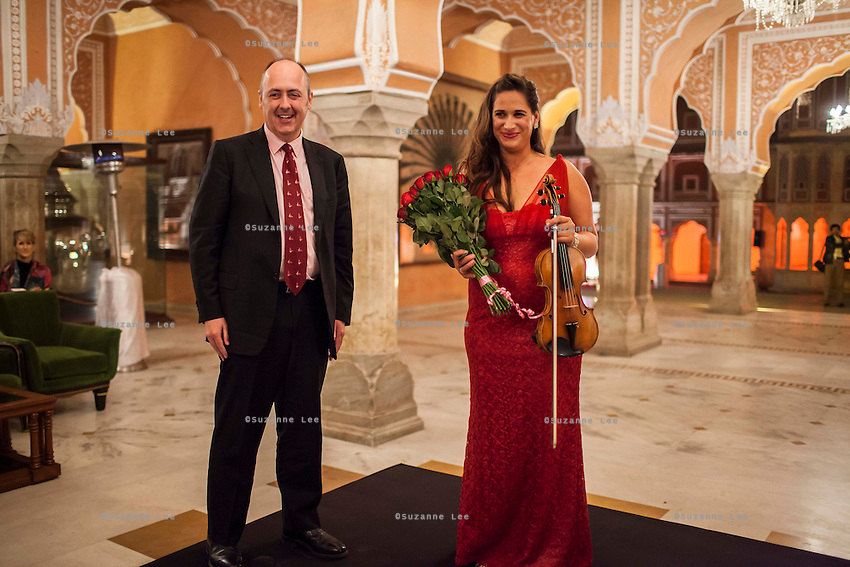 Australia's High Commissioner to India, Dr. Lachlan Strahan (left) praises Australian violinist Niki Vasilakis as he presents here with a bouquet of flowers after her solo violin concert played to a prominent audience, including the Jaipur Royal Family, and other VIPs during a recital at the OzFest Gala Dinner in the Jaipur City Palace, in Rajasthan, India on 10 January 2013. Photo by Suzanne Lee