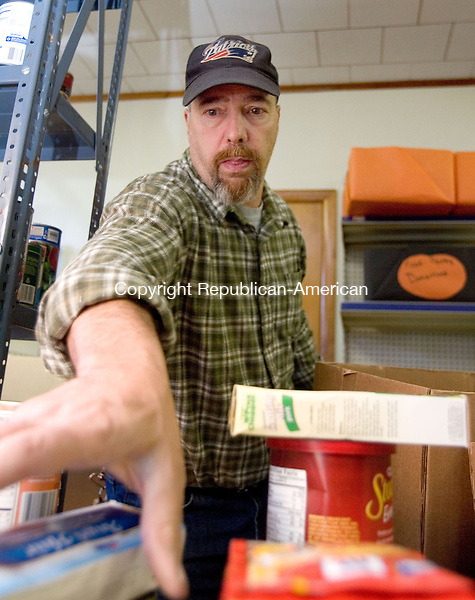 TERRYVILLE, CT. 26 November 2012-112612SV01-Mark Dunwells, volunteer, stocks shelves at the Plymouth Community Food Pantry in Plymouth Monday. The pantry handed out 150 turkey dinners with all the trimmings for Thanksgiving and is seeking donations for Christmas baskets. They will need to give out more they 150 baskets for the up coming holiday. Donations can be dropped off at the pantry of the volunteer ambulance..Steven Valenti Republican-American