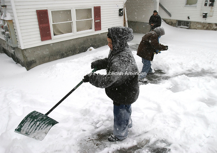 WATERBURY, CT, 03/16/07- 031607BZ06- From left- Nelson Mercedez, 13, of Waterbury, Davon Robinson, 13, of Waterbury, and Jivon Williams, 11, of Waterbury, shovel a driveway on Shelley Street in Waterbury Friday afternoon.  The kids said they were out shoveling driveways trying to earn spending money.  They said they would rather earn their own money instead of always asking their parents. <br /> Jamison C. Bazinet Republican-American
