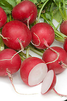 Radish 'Annabel' red cut open picked interior root vegetable, harvested on plate, showing white flesh and red outer skin
