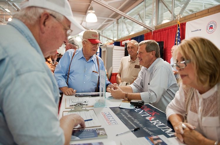 UNITED STATES - AUGUST 18:  Rep. Tom Latham, R-Iowa, second from right, talks with Dave Nichols, 72, of Anita, Iowa, at the Republican Party of Iowa booth at the Iowa State Fair in Des Moines, Iowa.  (Photo By Tom Williams/Roll Call)