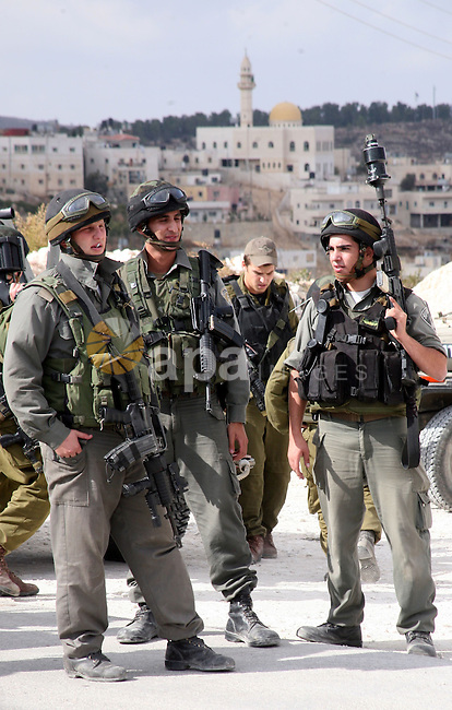Israeli soldiers stand guard during a protest against the controversial Israeli barrier in the West Bank village of al-Masarah, near Bethlehem, October 29, 2010. Israel says the barrier is needed for security, but Palestinians think of it as a land grab that undermines their promised state. Photo by Najeh Hashlamoun