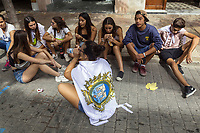 "Spain. Balearic Islands. Minorca (Menorca). Mahon. Cobble stone street. A group of young teenagers sit on the ground during the ""Festes de la Mare de Déu de Gràcia"" , a traditional summer festival. Maó (in Catalan) and Mahón (in Spanish), written in English as Mahon, is a municipality, the capital city of the island of Menorca, and seat of the Island Council of Menorca. The city is located on the eastern coast of the island, which is part of the autonomous community of the Balearic. In Spain, an autonomous community is a first-level political and administrative division, created in accordance with the Spanish constitution of 1978, with the aim of guaranteeing limited autonomy of the nationalities and regions that make up Spain. 7.09.2019 © 2019 Didier Ruef"