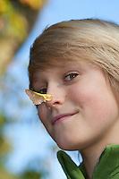 """Ahorn-Nase, Ahornnase, Kind, Junge hat Frucht, Samen, Flügelfrucht vom Ahorn auf die Nase geklemmt. Man kann sich die Frucht auf die Nase stecken, daher der Name """"Nasenzwicker"""". Man kann einen einzelnen Flügel am Ansatz etwas auseinander ziehen und ihn sich auf die Nase kleben. Acer"""