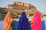 Rajasthani women in traditional clothes overlooking Blue City (old town) and Mehrangarh Fort; the blue houses were originally for Brahmins but non-Brahmins soon joined in, as the colour was said to deflect the heat and keep mosquitoes away, Jodphur, Rajasthan, India --- Model Released
