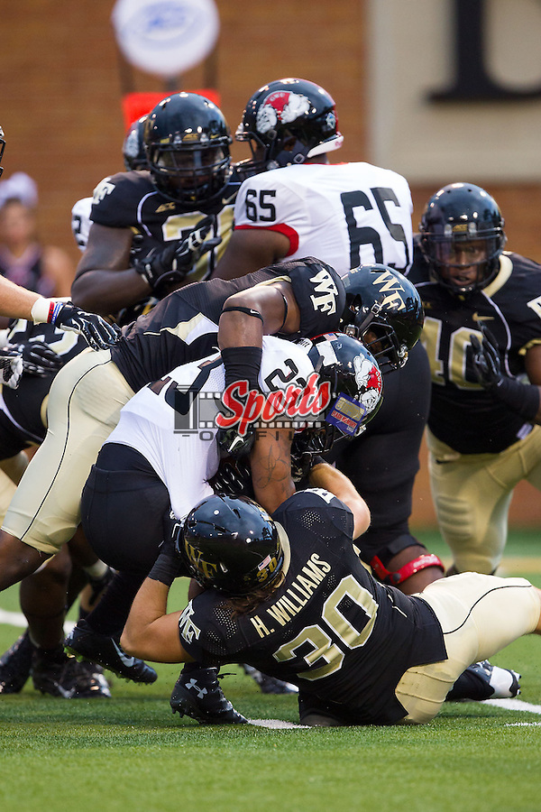 Juanne Blount (23) of the Gardner Web Runnin' Bulldogs is tackled by Marquel Lee (8) and Hunter Williams (30) of the Wake Forest Demon Deacons during first quarter action at BB&T Field on September 6, 2014 in Winston-Salem, North Carolina.   (Brian Westerholt/Sports On Film)