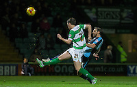 Paul Hayes of Wycombe Wanderers hits a shot at goal past Alex Lacey of Yeovil Town during the Sky Bet League 2 match between Yeovil Town and Wycombe Wanderers at Huish Park, Yeovil, England on 24 November 2015. Photo by Andy Rowland.
