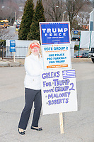 Supporters of US President Donald Trump hold signs outside the Holy Name Parish Hall polling place as people arrive to vote in the Massachusetts presidential primary on Super Tuesday in West Roxbury, Massachusetts, on Tue., March 3, 2020. The sign's references to Group 2 are in support of a pro-Trump slate of candidates in the Ward 20 local election.