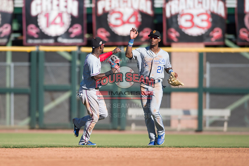 Surprise Saguaros right fielder Nick Heath (21), of the Kansas City Royals organization, celebrates a victory with Julio Pablo Martinez (40), of the Texas Rangers organization, after an Arizona Fall League game against the Scottsdale Scorpions at Scottsdale Stadium on October 26, 2018 in Scottsdale, Arizona. Surprise defeated Scottsdale 3-1. (Zachary Lucy/Four Seam Images)