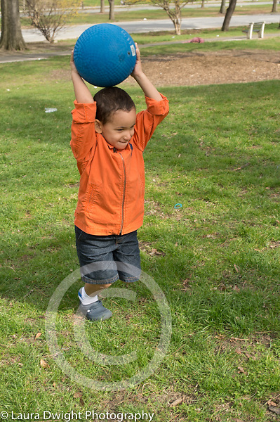 3 year old boy outside playing catch with large blue ball