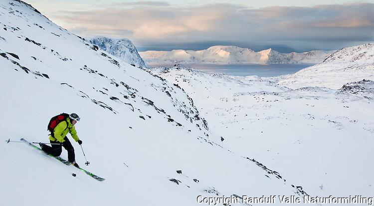 Mann kjører telemark ned fra Eidvågtind på Seiland. Sørøya i bakgrunnen. ---- Man skiing down Eidvågtind on Seiland.