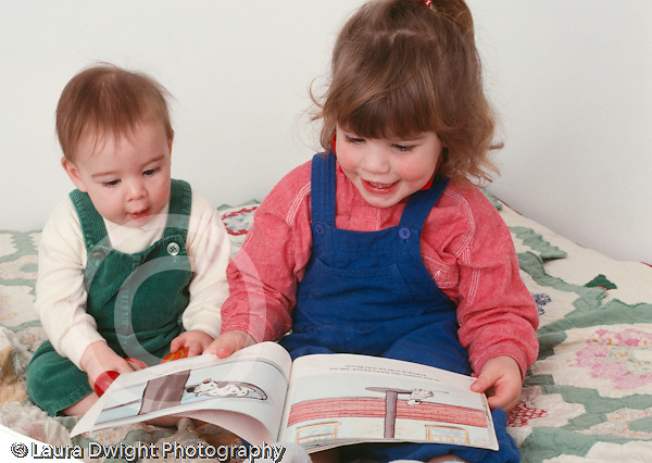 2 year old toddler girl looking at book with 7 month old sister horizontal