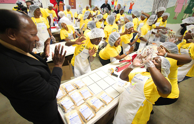 Iowa native and world-renowned opera singer Simon Estes, left, dances and sings with students from the Simon Estes Music High School in Capteown, South Africa, while packaging meals at Meals from the Heartland's West Des Moines warehouse on May 18.