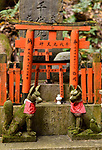 Foxes, Kitsune, at a small private worship Tsuka shrine altar, one of the thousands little Shinto shrines at Fushimi Inari Taisha head shrine in Fushimi Ward, Kyoto, Japan