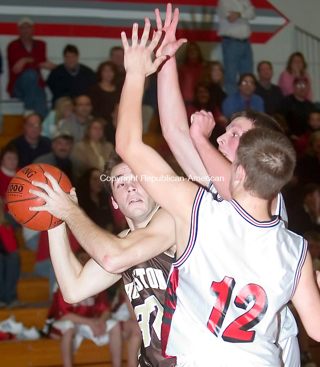 WINSTED, CT- 22 DEC 06- 122206JT19- <br /> Thomaston's Anthony Pesce tries to look past Northwestern's Kyle Case and Jason Gentile at Northwestern. Northwestern won 56-43.<br /> Josalee Thrift Republican-American