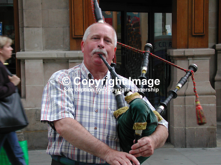 Bagpiper busker in city centre, Chester, England, UK. Ref: 200005630..Copyright Image from Victor Patterson, 54 Dorchester Park, Belfast, UK, BT9 6RJ..Tel: +44 28 9066 1296.Mob: +44 7802 353836.Voicemail +44 20 8816 7153.Skype: victorpattersonbelfast.Email: victorpatterson@mac.com.Email: victorpatterson@ireland.com (back-up)..IMPORTANT: If you wish to use this image or any other of my images please go to www.victorpatterson.com and click on the Terms & Conditions. Then contact me by email or phone with the reference number(s) of the image(s) concerned.