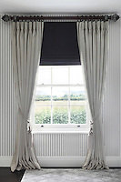 A Georgian sash window in the master bedroom, elegantly dressed in floor-to-ceiling pale grey drapes and a dark blue blind