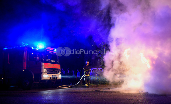 A firefighter attempts to extinguish a fire in a car set alight during demonstrations against the G20 summit in Hamburg, Germany, 7 July 2017. The summit, a meeting of the governments of the twenty largest world economies, begins on the 7 July and concludes on the 8 July. Photo: Axel Heimken/dpa /MediaPunch ***FOR USA ONLY***