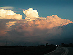 Cumulous thunderhead clouds before storm at sunset with auto