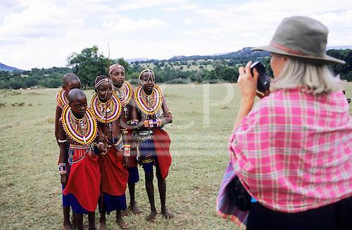 Lolgorian, Kenya. White female tourist taking a photograph of Maasai girls.