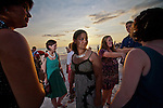 Wedding guests await the bride and groom's arrival for a sunset beach wedding on Anna Marie Island in Florida.