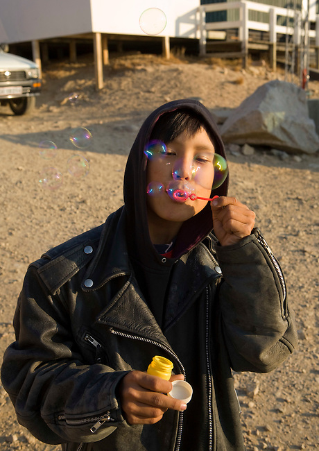 Abel, an Inuit boy, plays at blowing bubbles outside the shop in Qaanaaq. Northwest Greenland