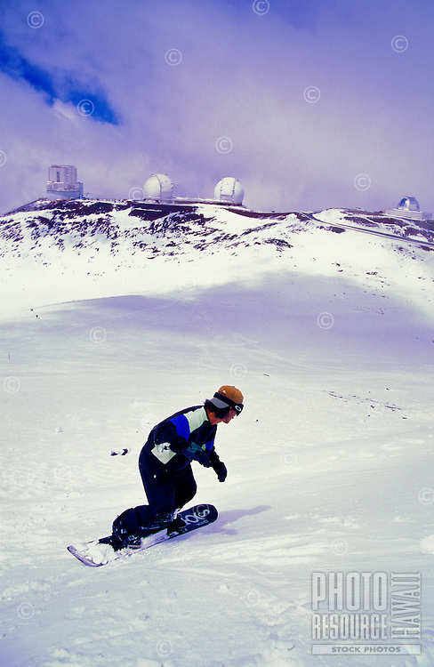 Closeup of man snowboarding down Mauna Kea. Row of white observatories and clouds blend with snow on mountain.