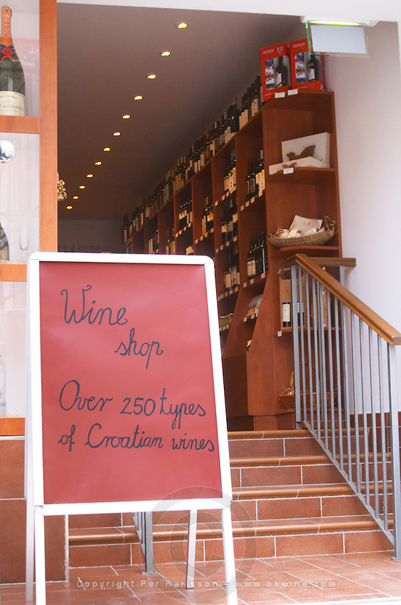 A red sign post with black writing advertising a wine shop with the text 'Wine shop, over 250 types of Croatian wines', view inside wine shop on the Luza Lodge Loggia Square Dubrovnik, old city. Dalmatian Coast, Croatia, Europe.
