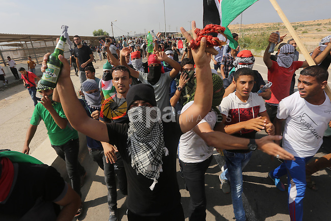Palestinians gather during clashes with Israeli security forces near the Erez border crossing between Israel and northern Gaza Strip on October 13, 2015. A wave of stabbings that hit Israel, Jerusalem and the West Bank this month along with violent protests in annexed east Jerusalem and the occupied West Bank, has led to warnings that a full-scale Palestinian uprising, or third intifada, could erupt. The unrest has also spread to the Gaza Strip, with clashes along the border in recent days leaving nine Palestinians dead from Israeli fire. Photo by Mohammed Asad