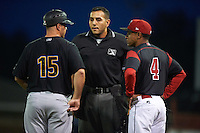 West Virginia Black Bears manager Wyatt Toregas (15) and Batavia Muckdogs manager Angel Espada (4) talk with umpire Raul Moreno during a game on August 20, 2016 at Dwyer Stadium in Batavia, New York.  Batavia defeated West Virginia 7-2. (Mike Janes/Four Seam Images)