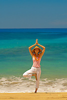 Young woman standing on Makaha beach in Yoga pose
