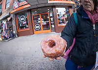 "A donut aficionado holds the newly released Dunkin Donuts' ""Croissant Donut"" in New York on Saturday, November 8, 2014. The 300 calorie pastry is the chain's attempt to capitalize on the ""cronut craze"" created by the baker Dominique Ansel. (© Richard B. Levine)"
