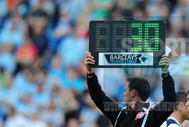 The fourth official holds up the substitute board
