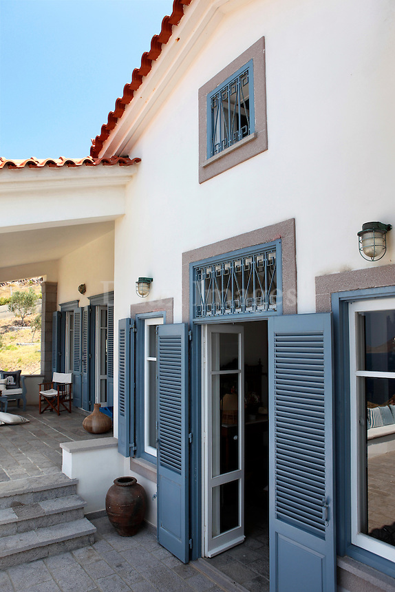 facade of the house..Sigalas' house in Limnos, Greece, preserves the architectural elements of the traditional homes on the island.  It was built with high-ceilinged rooms, a main hallway and interior windows.