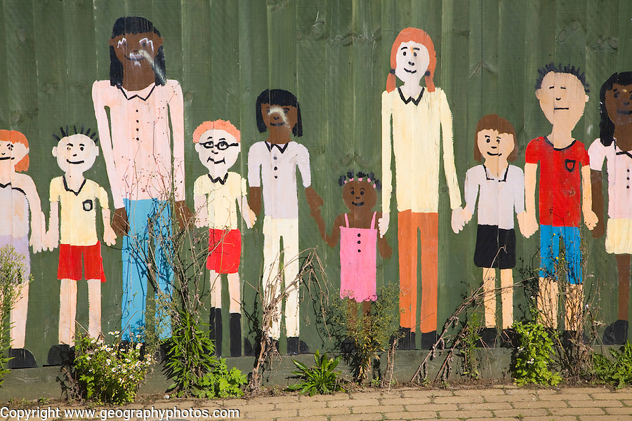 Mural painted on wooden fence of children of different ages holding hands, UK