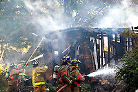 Firefighters from Osolo, Cleveland and Bristol extinguish a fire at an abandoned home located on Medford Street in Elkhart (Osolo Township) on the evening of Wednesday, June 30, 2010. The cause of the fire is currently unknown; no people were injured as a result of the fire.