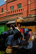 A man reads the news paper while a labourer carries a basket of vegetables in the New Market area in Kolkata, West Bengal  on Friday, May 26, 2017. Photographer: Sanjit Das