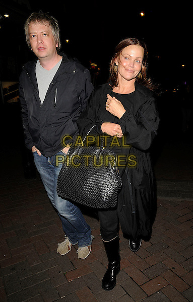 """GUEST & BELINDA CARLISLE.The """"Without You I'm Nothing"""" press night, Leicester Square, London, England..May 26th, 2009.full length black jacket coat weave bag purse wellies wellington boots jeans denim.CAP/CAN.©Can Nguyen/Capital Pictures."""