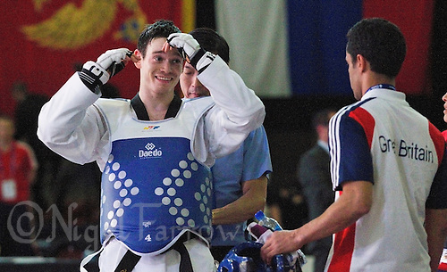 05 MAY 2012 - MANCHESTER, GBR - Aaron Cook (GBR) of Great Britain talks with his national team coach, Joseph Salim, after winning the men's 2012 European Taekwondo Championships -80kg category final at Sportcity in Manchester, Great Britain against Ramin Azizov of Azerbaijan when the referee penalised Azizov for stepping out of the field of play in the final second of the last round to give Cook the title .(PHOTO (C) 2012 NIGEL FARROW)