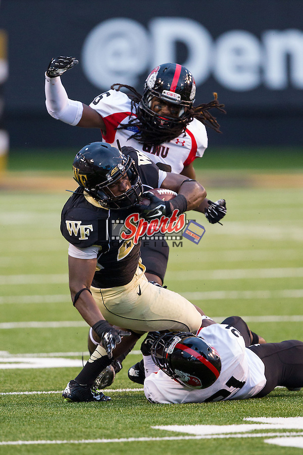 Isaiah Robinson (21) of the Wake Forest Demon Deacons is tackled by Calvin Smith (21) and Aaron Cook (26) of the Gardner Web Runnin' Bulldogs during first half action at BB&T Field on September 6, 2014 in Winston-Salem, North Carolina.  The Demon Deacons defeated the Runnin' Bulldogs 23-7.   (Brian Westerholt/Sports On Film)