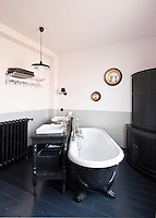 A black-painted roll-top bath is positioned in the centre of this bathroom with a table supporting a pair of oblong wash basins alongside it