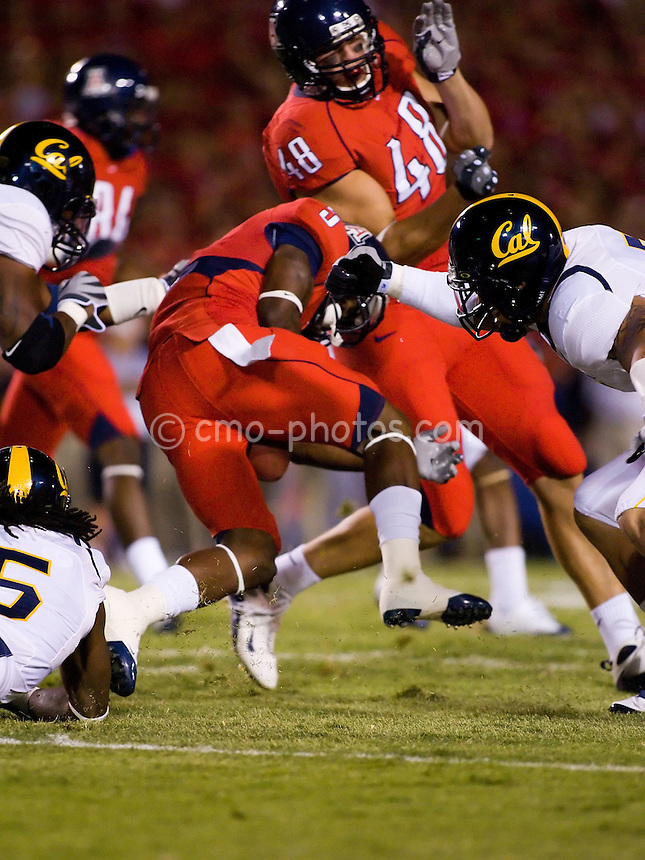 Oct 18, 2008; Tucson, AZ, USA; Arizona Wildcats running back Nic Grigsby (5) fumbles the ball between his legs as three California Golden Bears defenders attempt to tackle him in the first quarter of a game at Arizona Stadium.