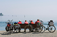 DEU, Deutschland, Baden-Wuerttemberg, Bodensee, Konstanz: Radfahrer bei Rast auf einer bank am Bodensee | DEU, Germany, Baden-Wuerttemberg, Lake Constance, Constance: cyclists resting on a banch